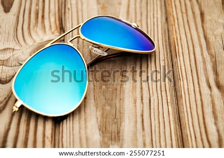 blue mirrored sunglasses on the wooden background close up. horizontal - stock photo