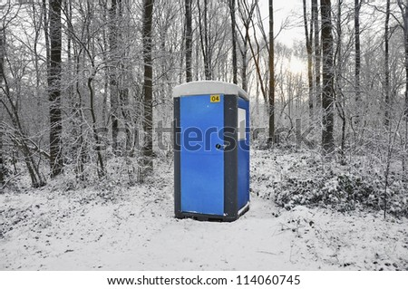 Blue mobile toilet cabin in a snow covered forest - stock photo