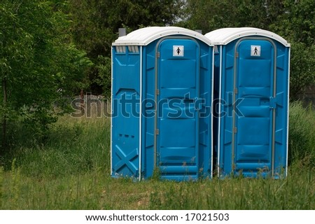 Blue mobile toilet cabins in an outdoor scene - stock photo