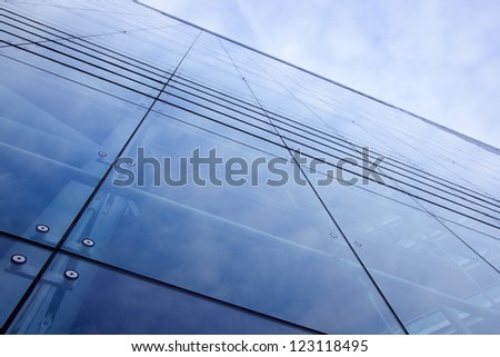 blue modern facade of office building reflecting sky - stock photo