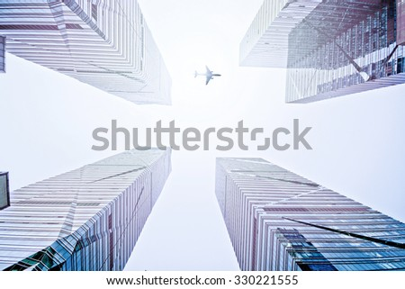 blue modern glass reflective skyscrapers in city downtown district with sun light and airliner - stock photo
