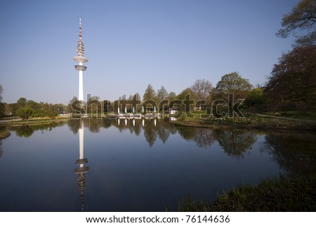 Blue morning with Television Tower Hamburg and lake from Botanic Garden. - stock photo