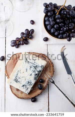 Blue mould, mold cheese with fresh grape on a white wooden background - stock photo