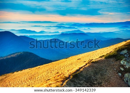 Blue mountains and hills over beautiful sunset - stock photo