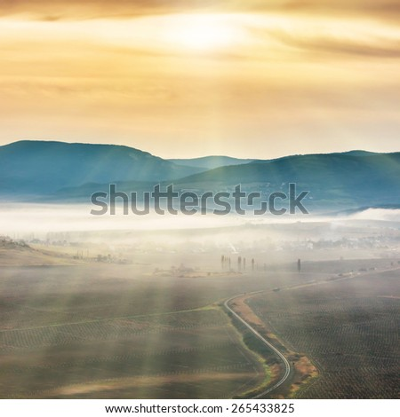 Blue mountains and road covered with mist against sunset. Bright sun shining on the sky
