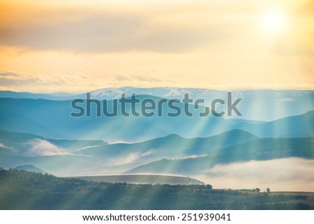 Blue mountains covered with mist against sunset. Bright sun shining on the sky - stock photo