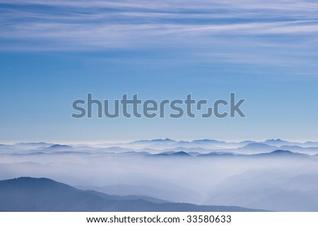 Blue mountains on a horizon with gentle blue sky with clouds