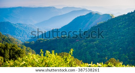 Blue mountains panorama - Cardamom Hills in the haze on the road Alleppey-Kumily, Kerala, India - panoramic 1x2 photo - stock photo