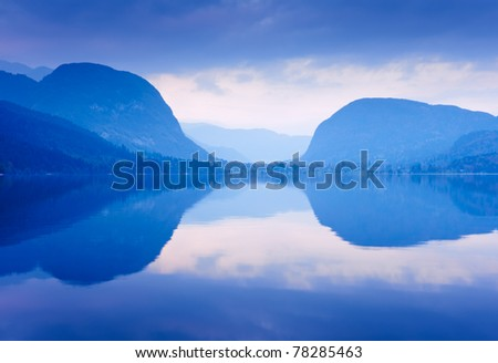 Blue mountains reflected in lake water. Bohinj lake, Slovenia. - stock photo