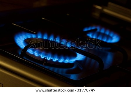 Blue natural gas flames on a kitchen oven