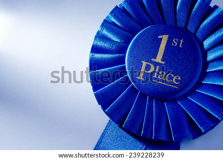 Blue 2nd place winners rosette or badge with a pleated ribbon and gold lettering, close up view over white with copyspace - stock photo