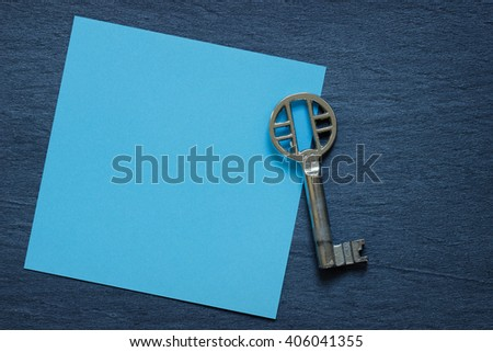 Blue note with vintage key on dark background