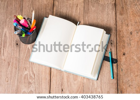 Blue Notebook and pen on the old wooden floor - stock photo