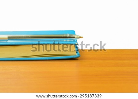 blue notebook put on wooden table in class room - stock photo
