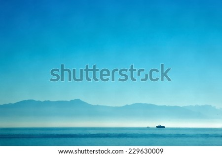 Blue ocean, blue sky and blue mountains silhouette. Stylized as painting. - stock photo