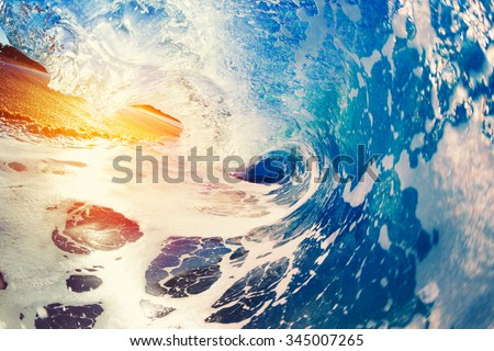 Blue Ocean Wave Crashing at Sunrise - stock photo