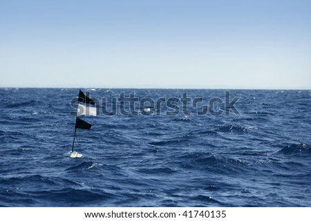 Blue ocean with longline flag fishing floating beacon in Spain - stock photo