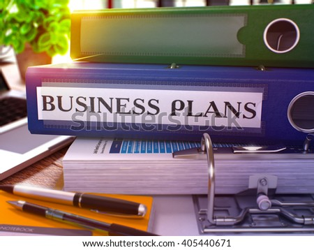 Blue Office Folder with Inscription Business Plans on Office Desktop with Office Supplies and Modern Laptop. Business Plans Business Concept on Blurred Background. Business Plans - Toned Image. 3D.