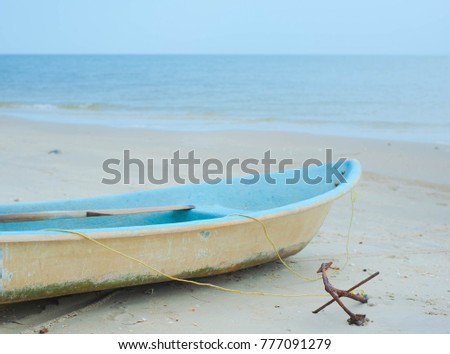blue old boat on the beach,Old boat anchored on the beach with sky and sea