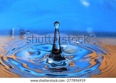 Blue- orange water drop splashing with waves - stock photo