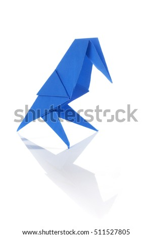 Blue origami bird on black wall isolated over white background with reflection