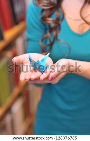 Blue origami crane in woman hands indoors - stock photo