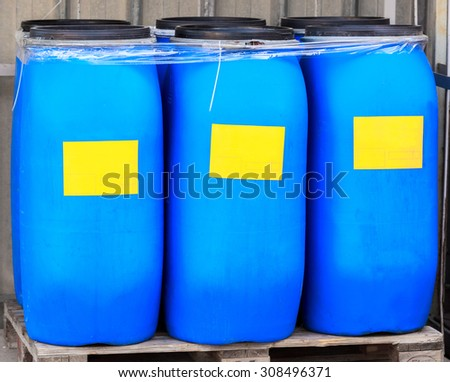 Blue packed barrels with yellow labels a chemical plant - stock photo