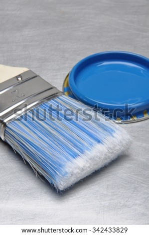Blue paint can lid with brush on grey metal background - stock photo