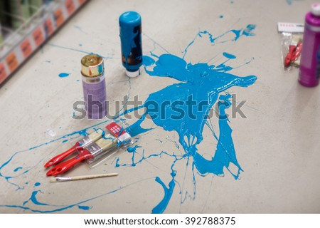 Blue paint spill stain accident drop on the grey floor with brushes and paint tubes in the hardware store or hobby market. Handmade art painting.  - stock photo