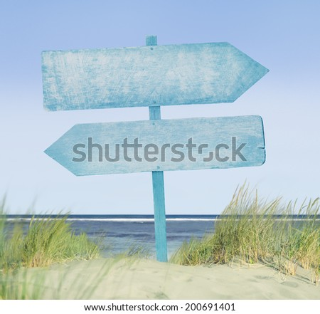 Blue Painted Wooden Sign on Beach - stock photo