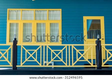 blue pannel and yellow window door  - stock photo