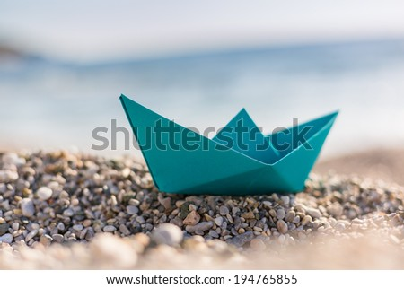 Blue paper boats on beach outdoors  - stock photo
