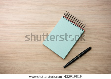 Blue paper memo pad with pen on wooden table or desk. - stock photo