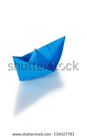 Blue paper ship on a glass with reflection - stock photo