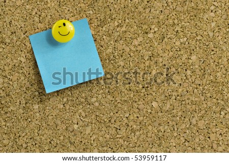 Blue paper with expressive thumb tack on bulletin board - stock photo