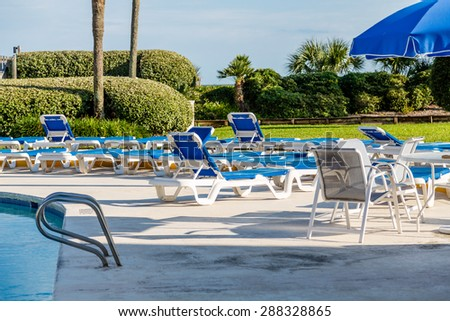 Blue patio furniture on deck between swimming and ocean - stock photo