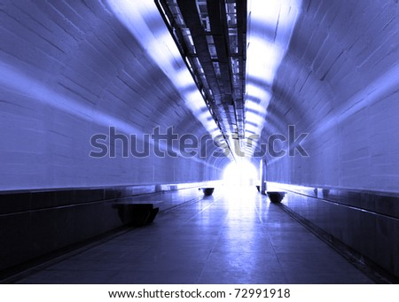 blue pedestrian tunnel with light at the end - stock photo