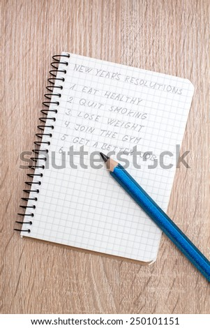 Blue pencil and notepad with New Year's resolutions - stock photo