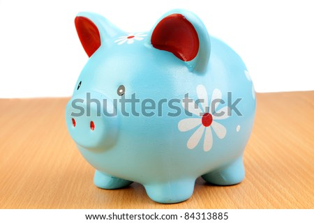 Blue piggy-bank on a wooden table isolated on white background