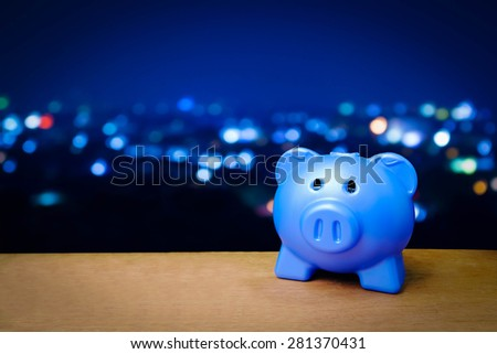 blue piggy bank on blur light in city background - stock photo