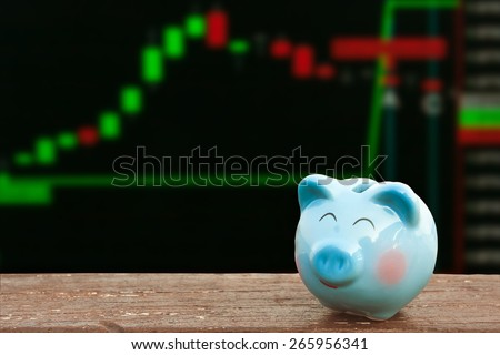 blue piggy bank on wooden table over share of stock; share of business background,money and saving concept. - stock photo