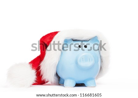 blue piggy bank wearing santas hat on white background - stock photo