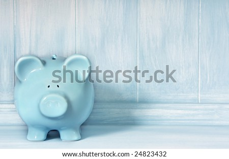 Blue piggybank with blue brushed timber background.  Lots of copy-space. - stock photo