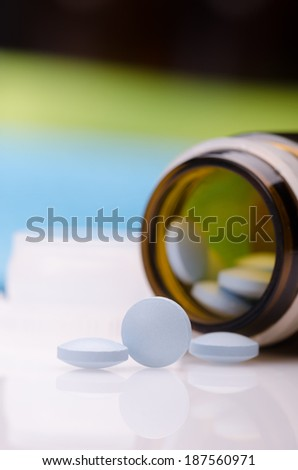 Blue pills in a brown bottle against blue green background  - stock photo