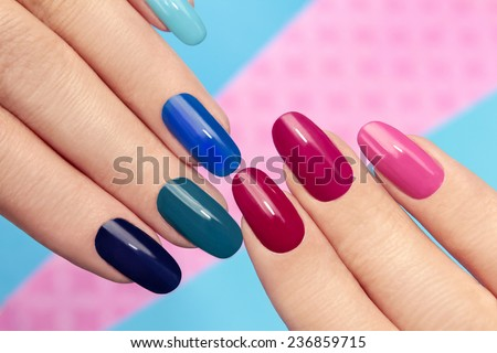 Blue pink nail Polish on long nails on a colored background. - stock photo