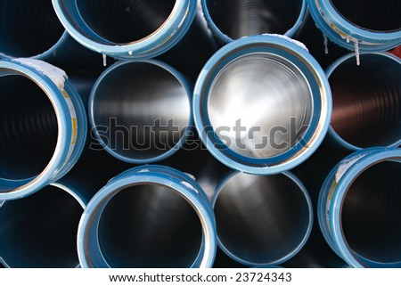 blue pipes stacked in construction site, pattern closeup - stock photo