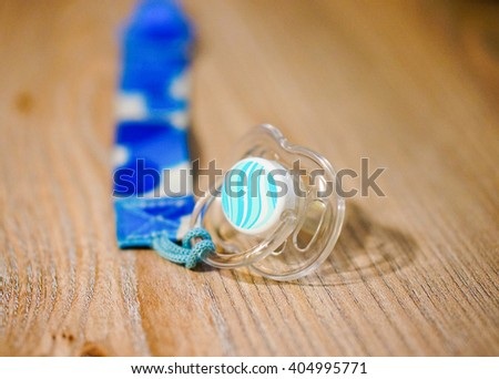 Blue plastic baby pacifier on wooden table - stock photo