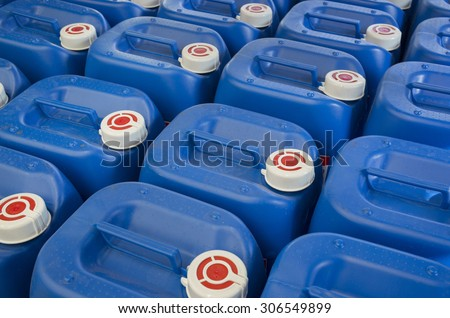Blue plastic barrels containing chemicals in storage - stock photo