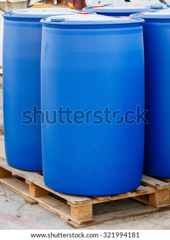 Blue plastic barrels on pallet in a chemical plant - stock photo