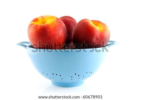 blue plastic colander with fresh peaches over white background